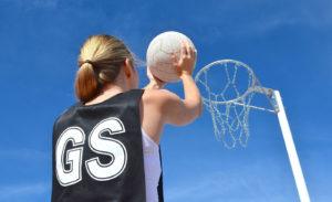 Girl shooting ball into netball hoop