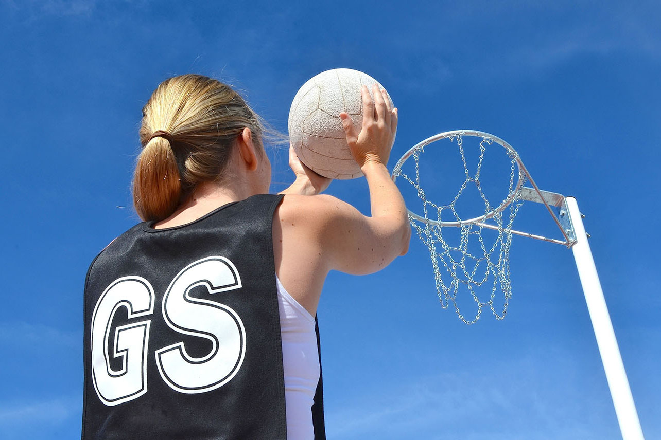 Girl shooting ball into netball hoop
